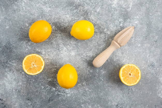 Fresh organic lemons and squeezer on grey surface.