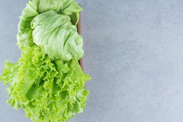 Foglie di lattuga fresca organica in ciotola su sfondo grigio.