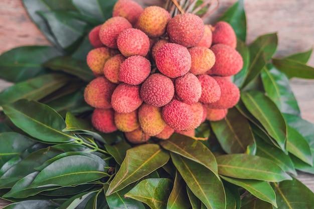 素朴な木の表面に新鮮な有機ライチフルーツとライチの葉