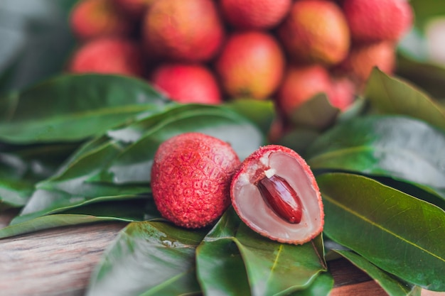 素朴な木製の新鮮な有機ライチフルーツとライチの葉