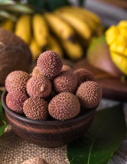 대나무 바구니와 오래된 나무 배경에 있는 신선한 유기농 리치 과일, 흐릿한 배경 선택적 초점.