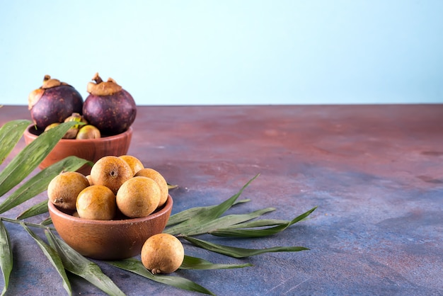 Fresh organic lychees with palm leaf in a bowl on stone background. raw diet or vegan food concept.