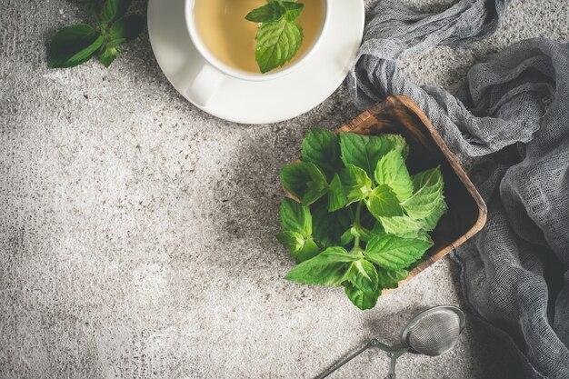 灰色の背景に新鮮な有機ミントとお茶。