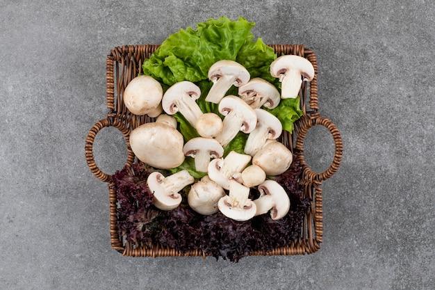 Свежие органические грибы с салатом в корзине.