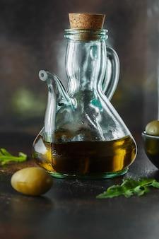 暗い背景の水差しに新鮮な有機オリーブオイル。フードフォトグラフィー。おいしいオリーブオイルのボトル。油と缶詰のオリーブのガラスの水差し