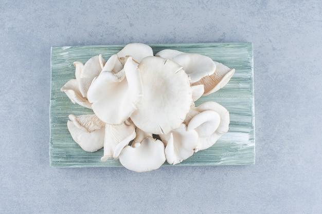 Fresh organic oyster mushrooms on wooden board.