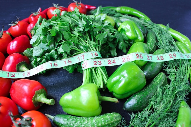 Fresh organic parsley, tomatoes, red peppers, green peppers, fennel, dill and cucumber with green centimeter top view, diet concept