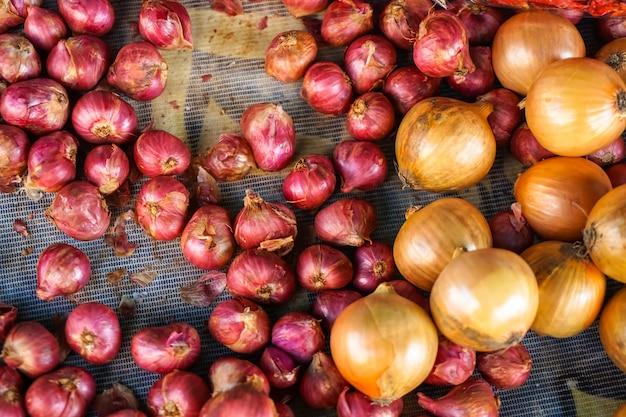 食品原料のための地元の市場で販売されている赤シャロットとタマネギの新鮮な有機杭