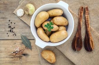 Fresh organic potatoes on rustic wooden .