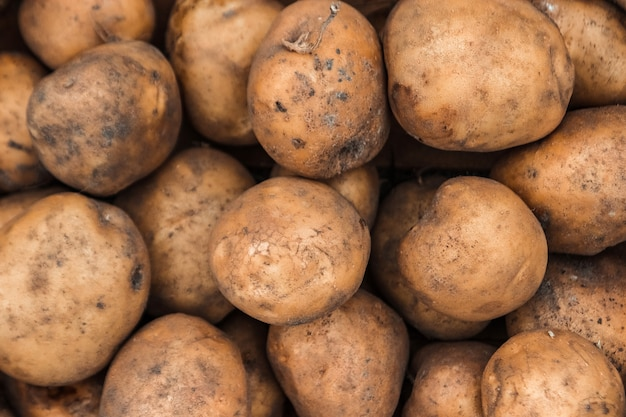 Fresh organic potatoes on stand in supermarket background