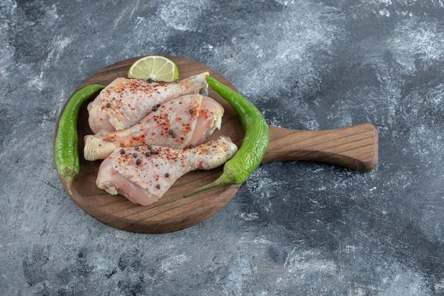 Cosce di pollo crudo biologico fresco e peperoni verdi sul tagliere di legno.
