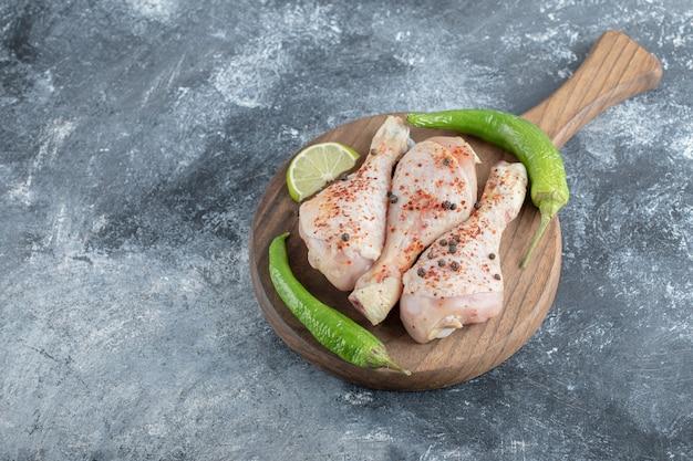Bacchette di pollo crudo biologico fresco sul tagliere di legno su sfondo grigio.