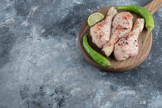 Bacchette di pollo crude organiche fresche sul tagliere di legno.
