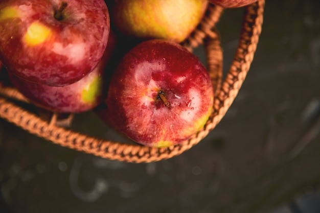 Fresh organic red apples in a basket on black