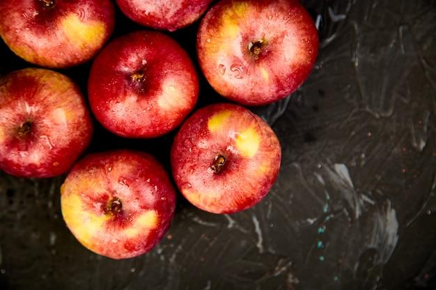 Fresh organic red apples on black