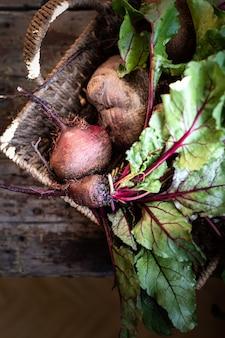 Свежие органические красные свеклы с листьями в плетеной корзине на деревянном столе. натуральные органические овощи. осенний урожай. простоватый