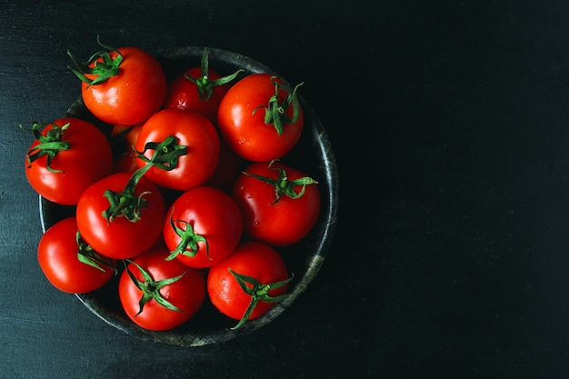 Fresh organic red tomatoes in black plate, close up, healthy concept, top view