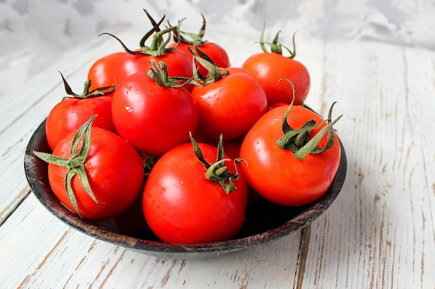 Fresh organic red tomatoes in black plate on white wooden table with green and red and chili peppers, green peppers, black peppercorns, salt, close up, healthy concept