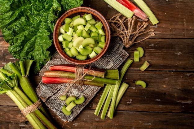 まな板の上の新鮮な有機ルバーブ、調理ルバーブ。食品レシピの背景。閉じる