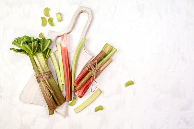 Fresh organic rhubarb on a white old wooden table. banner menu recipe place for text top view