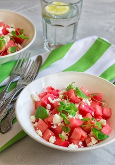Fresh organic salad with watermelon, feta cheese and mint on  light gray concrete table. healthy vegetarian food.