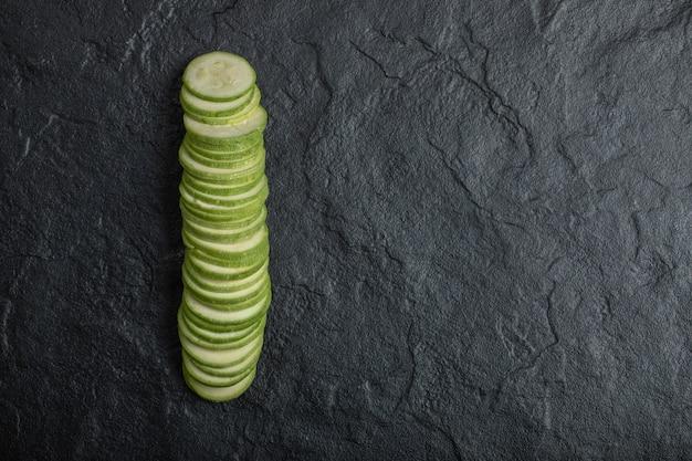 Zucchine affettate organiche fresche su fondo nero.