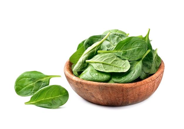 Салат из свежего органического шпината в деревянной тарелке.