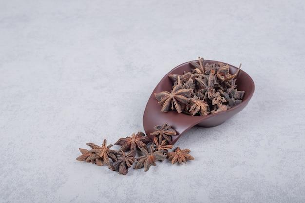 Fresh organic star anise spice fruits on dark plate.