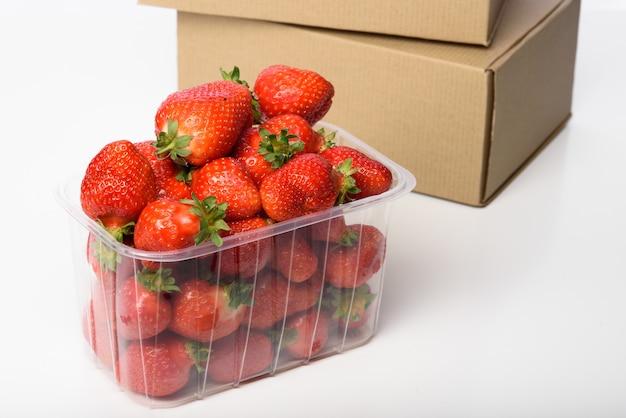 プラスチックの箱とクラフトボックスに新鮮な有機栽培のイチゴ。有機食品の配達。有機イチゴの包装。クラフトボックスとオーガニックフード。