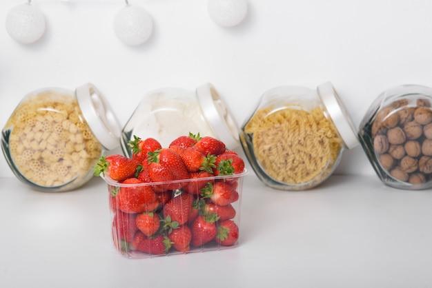 キッチンのプラスチックの箱に新鮮な有機栽培のイチゴ。オーガニック製品の配達。有機イチゴの包装。