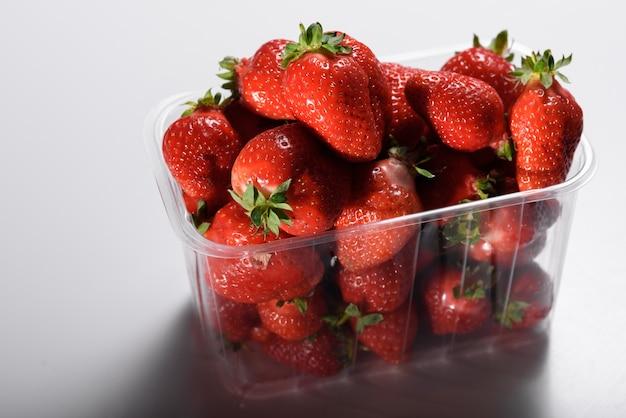 白い壁にプラスチックの箱で新鮮な有機栽培のイチゴ。オーガニック製品の配達。有機イチゴの包装。