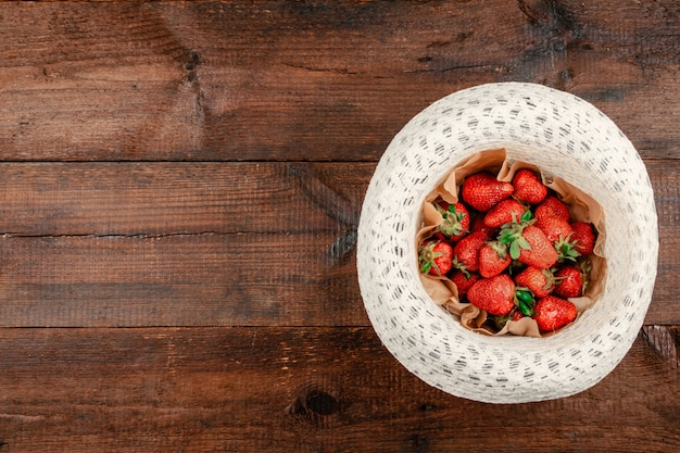 Fresh organic strawberries on round straw hat