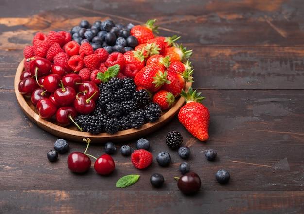新鮮な有機夏のベリーは、暗い木製のテーブルの背景に丸い木製トレイに混ぜます。ラズベリー、イチゴ、ブルーベリー、ブラックベリー、チェリー。上面図