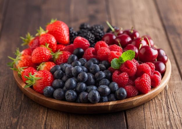 新鮮な有機夏のベリーは、明るい木製のテーブルの背景に丸い木製トレイに混ぜます。ラズベリー、イチゴ、ブルーベリー、ブラックベリー、チェリー。上面図