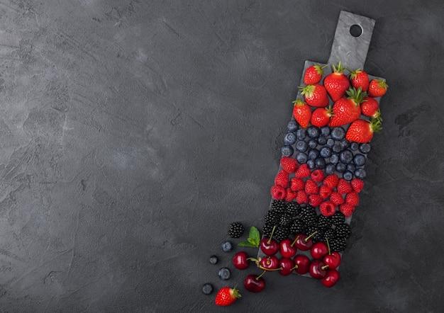 新鮮な有機夏のベリーは、暗いキッチンテーブルの背景に黒い大理石のボードにミックスします。ラズベリー、イチゴ、ブルーベリー、ブラックベリー、チェリー。上面図