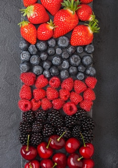 新鮮な有機夏のベリーは、暗いキッチンテーブルの背景に黒い大理石のボードにミックスします。