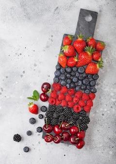 新鮮な有機夏のベリーは、明るいキッチンテーブルの背景に黒い大理石のボードにミックスします。ラズベリー、イチゴ、ブルーベリー、ブラックベリー、チェリー。上面図