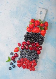 新鮮な有機夏のベリーは、青いキッチンテーブルの背景に白い大理石のボードにミックスします。ラズベリー、イチゴ、ブルーベリー、ブラックベリー、チェリー。上面図