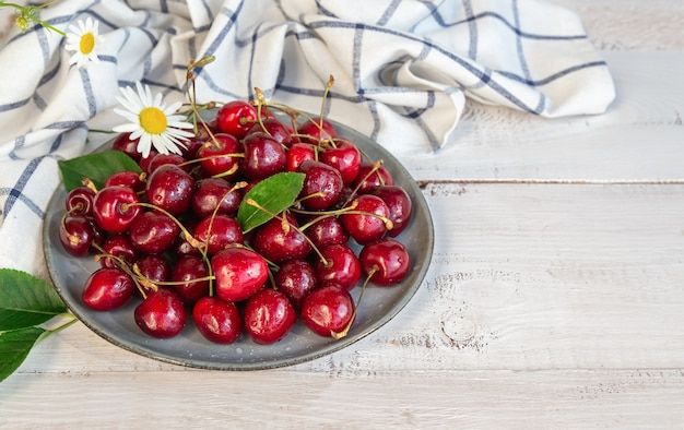 Fresh organic sweet cherries on plate at white wooden surface.