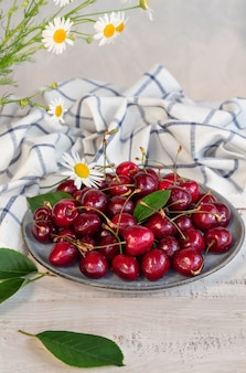 Fresh organic sweet cherries on plate at white wooden table.