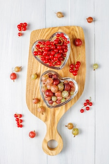Fresh organic sweet gooseberries and red currants in bowls