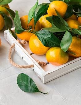 Свежие органические мандарины с листьями в белом деревянном подносе на светлом фоне бетона.