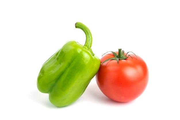 Pomodoro e pepe organici freschi isolati su superficie bianca.