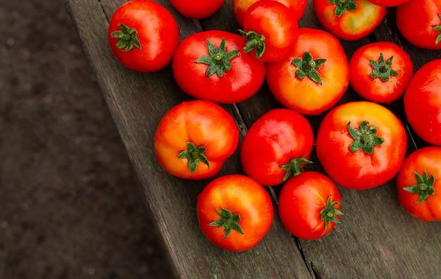 素朴な木製のテーブルの農場からの新鮮な有機トマト。バイオとエコフード