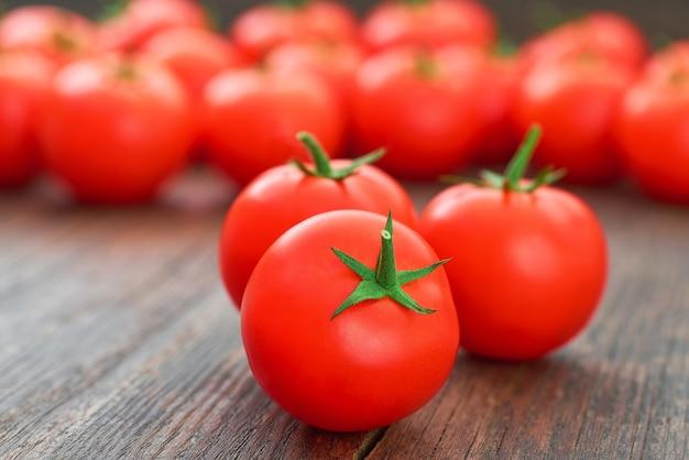 소박한 나무 테이블에 신선한 유기농 토마토입니다.