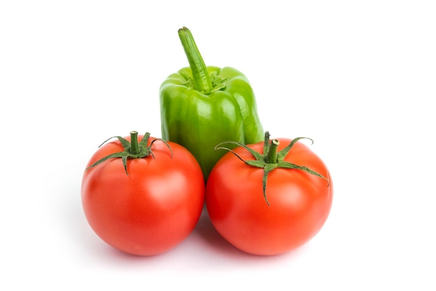 Pomodori e pepe organici freschi sopra fondo bianco.