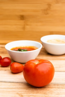 Fresh organic tomatoes and sauce on wooden table