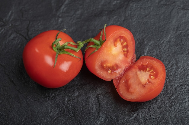 Fresh organic tomatoes. whole or half cut tomatoes on black background.