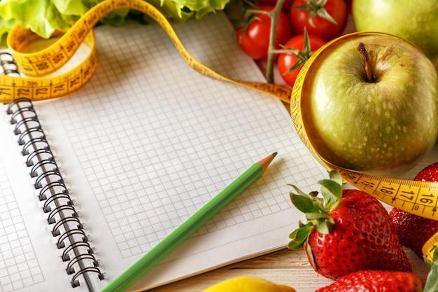 新鮮な有機野菜や果物、木製の表面に空白のノートブックとペンを開く