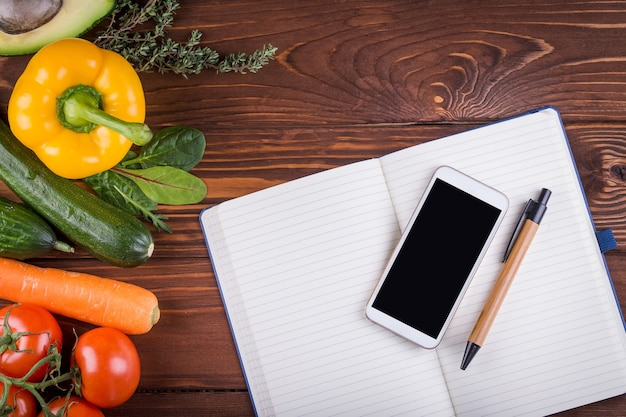 Свежие органические овощи и фрукты. перец, помидор, авокадо, открытая пустая тетрадь, телефон и ручка на деревянном фоне. концепция здорового питания и здорового образа жизни. вид сверху